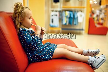 little girl sitting on sofa in