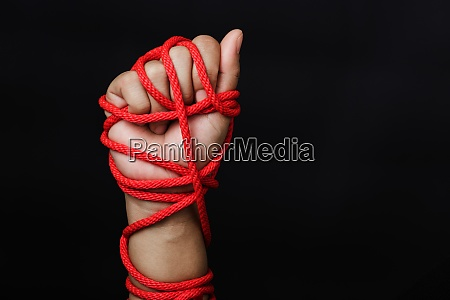 woman hand tied up with rope