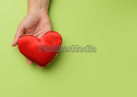 female hand holds red textile heart