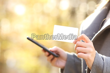 woman buying online with phone showing