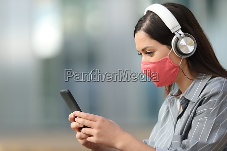 woman with mask listening to music