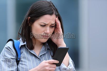 worried student checks smart phone message