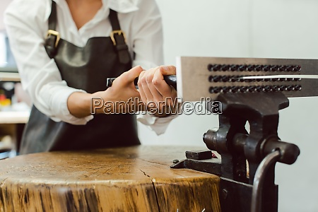 jeweler in her workshop pulling wire