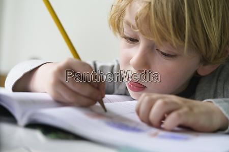 boy 4 5 doing homework