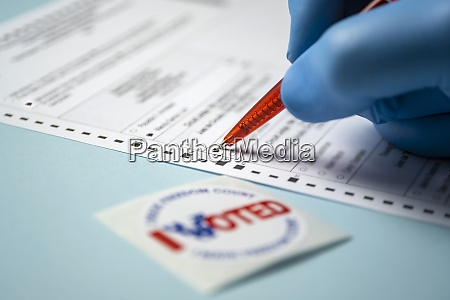 badge and hand filling voting form