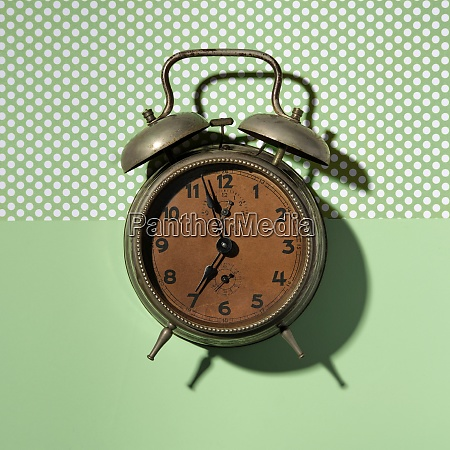 vintage alarm clock on green background