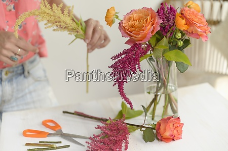 woman making floral arrangement