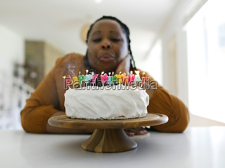 woman blowing candles on birthday cake