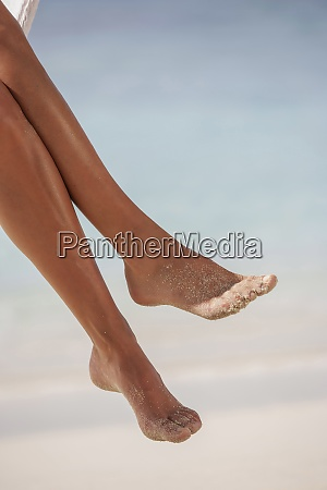 womans legs at tropical beach
