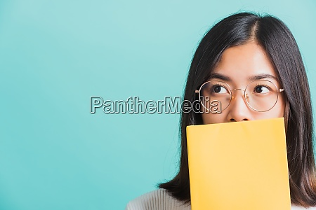 woman hiding behind an open book