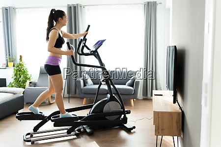 woman training on elliptical trainer online