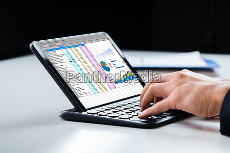 analyst using spreadsheet report on tablet