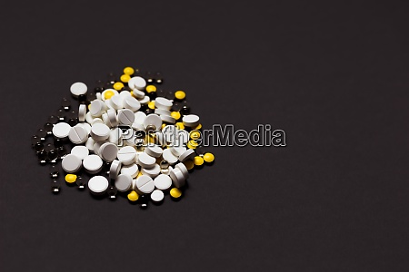 medicines spilling out on dark gray