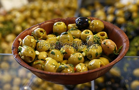 green olives in wooden bowl on