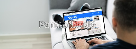 man using computer reading electronic news