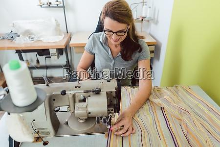 seamstress sews deco fabric on sewing