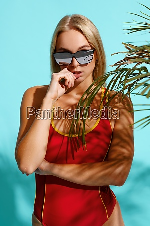 sportive woman in red swimsuit poses