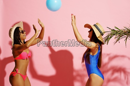 two women in swimsuits play with