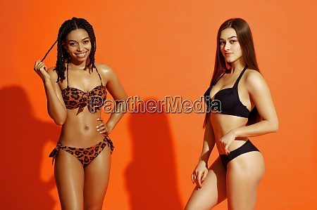 attractive women in swimsuits on orange