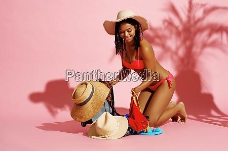 happy woman in swimsuit unpacks her