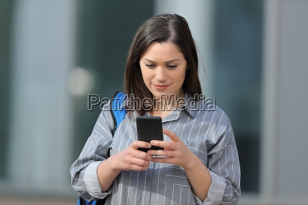 student checking smartphone walking in a