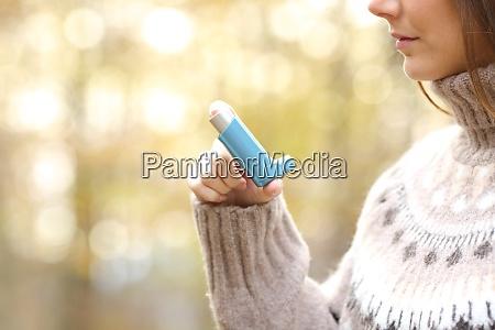 woman hand holding asthma inhaler ready