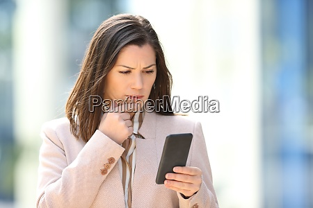 worried businesswoman reading message on phone