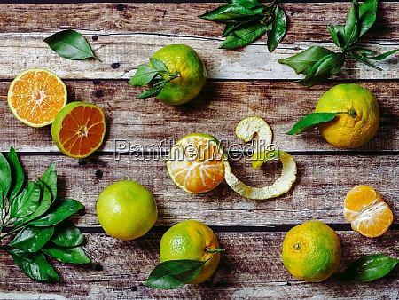 green mandarins on wooden background top
