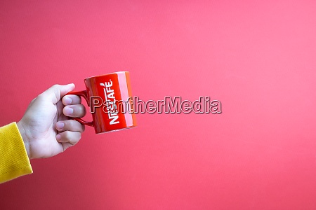 hand holding nescafe mug on red