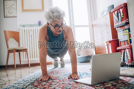 woman following online yoga class