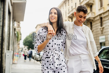 young lesbian couple walking arm in