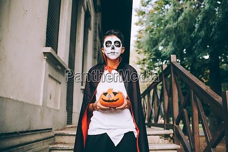 boy in halloween costume holding jack