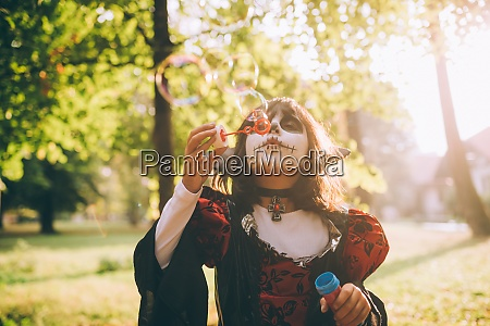 girl in halloween costume blowing bubbles