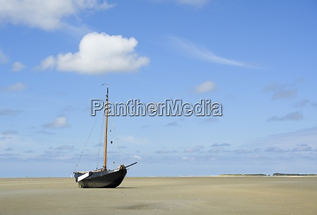 a flatbottom sailing ship is beached