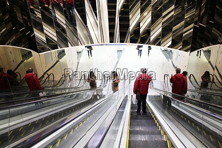 people ride escalator with mirrored walls