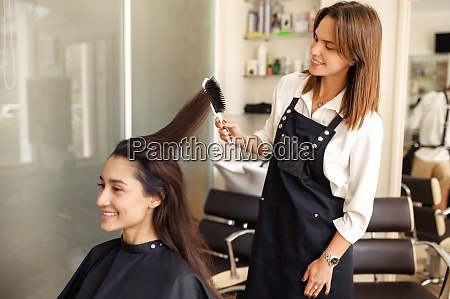 hairdresser works with comb hairdressing salon