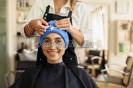 hairdresser puts towel on womans hair