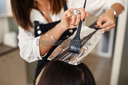 hairdresser works with customer hair closeup
