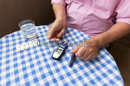 senior man using glucometer checking blood