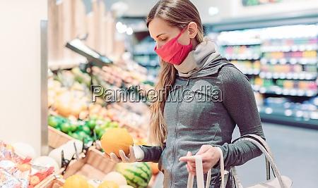 woman shopping in supermarket during coronavirus