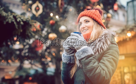 beautiful woman drinking mulled wine on