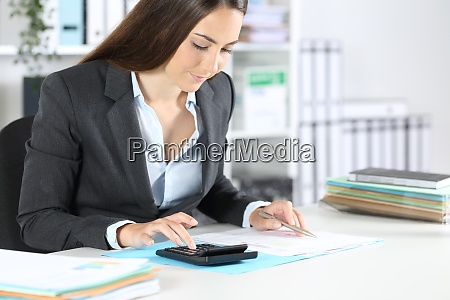 bookkeeper calculates on calculator sitting at