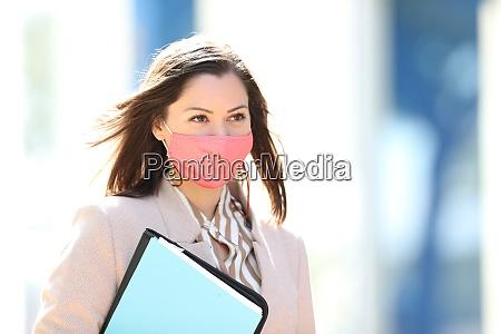 businesswoman with mask avoiding coronavirus walking