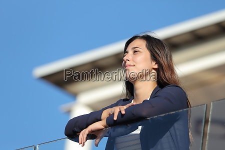 woman contemplating views from apartment balcony
