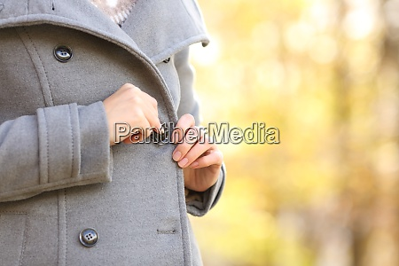 woman hand fastening a button on