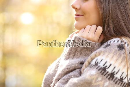 woman heating grabbing sweater collar in
