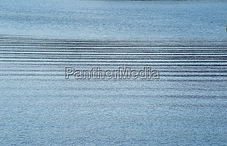 horizontal ripples across tranquil blue water