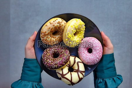 two hands holding plate of colourful