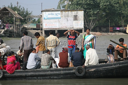 wooden boat crosses river in gosaba