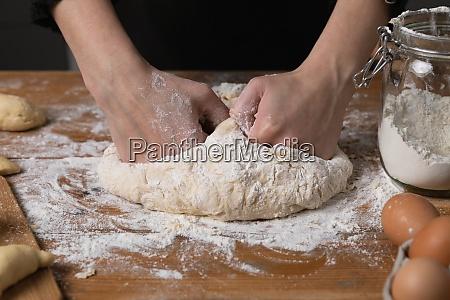 young beautiful woman kneading dough at